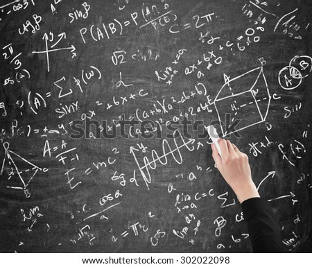 A woman's hand is writing math calculations on black chalk board. Analyst.