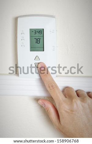 A woman's hand setting the room temperature on a modern digital programmable thermostat - stock photo