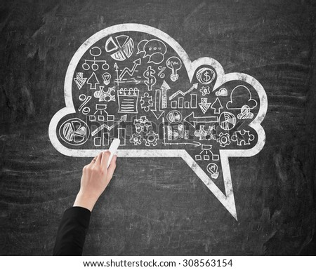 A woman's hand which is drawing a cloud with the range of business icons on the black chalkboard. - stock photo