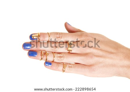 A woman's hand with many different gold rings on her fingers - stock photo
