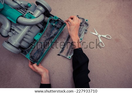 A woman's hands are cleaning and repairing a vacuum cleaner - stock photo