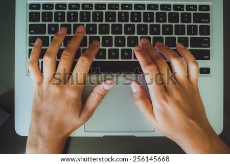 A woman's hands are typing on a laptop computer keyboard. The monitor is visible in the image, but it is not clear what she is working on. - stock photo