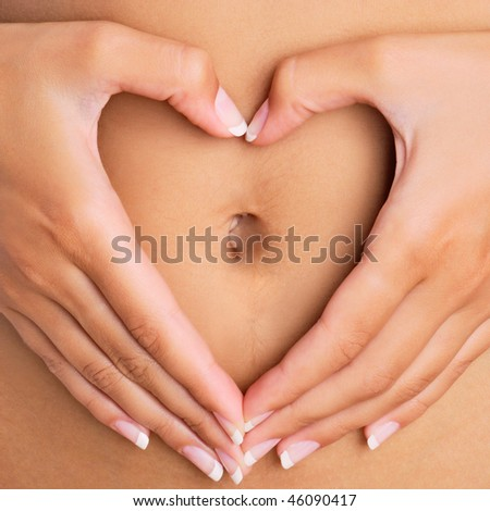 A woman's hands forming a heart symbol around navel - stock photo
