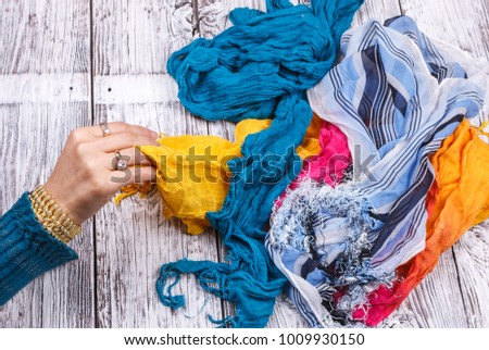 A woman's jewelry adorned hand is reaching for a scarf in a pile.