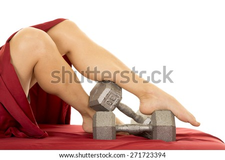 a woman's legs in bed with a red sheet, her legs and feet are on weights. - stock photo