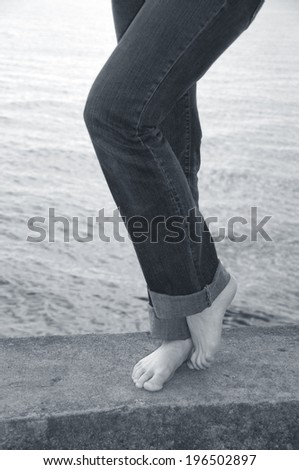 A woman's legs in jeans with bare feet standing on a cement pier at the beach.