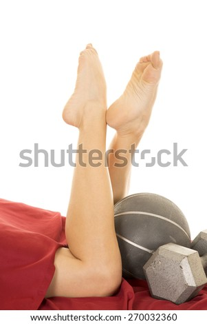 A woman's legs up with weights and medicine ball. - stock photo