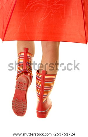 A woman's legs walking away with an umbrella.  She is in her red rain boots. - stock photo