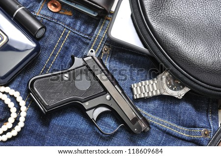 A woman's purse and  gun and accessories - stock photo