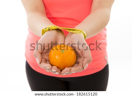 a woman's wrist trapped together by a measuring tape with a orange in the middle of her hands a concept showing how hard it is to keep fit in diet on a white background slave to healthy nutrition  - stock photo