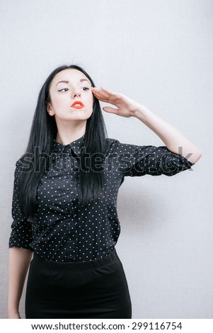A woman salutes to the head, swears the oath. On a gray background.