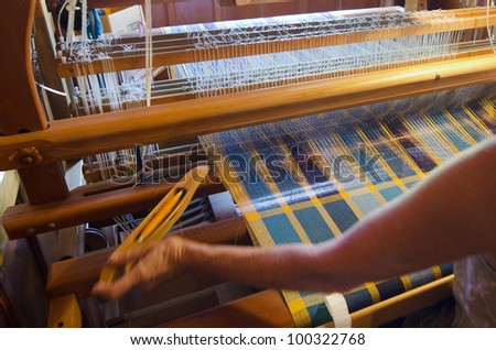 A woman saws on a loom.