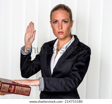 a woman says as a witness in court in a lawsuit. is sworn in and swears on the bible. - stock photo