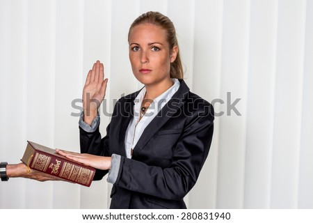 a woman says as a witness in court in a lawsuit. will be sworn in and swears on the bible. - stock photo
