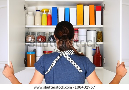 A woman seen from behind opening the doors to a fully stocked pantry. The cupboard is filled with various food stuff and groceries all with blank labels. Horizontal format the woman is unrecognizable.