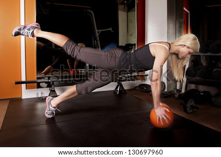 A woman showing off her strength by doing a push up on a ball with one leg up.