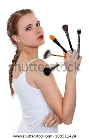 a woman showing some make-up pencils - stock photo