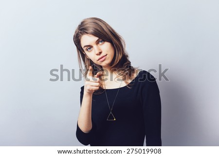 A woman shows a finger forward  - stock photo