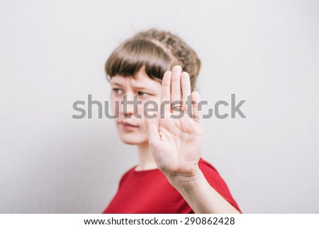 A woman shows a hand stop. On a gray background. - stock photo