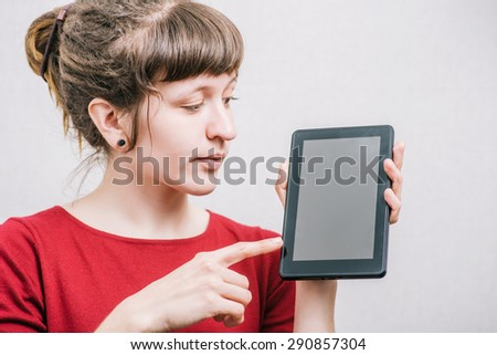 A woman shows  on the Digital Tablet. On a gray background.