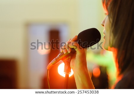 A woman signing live concert focus on microphone - stock photo