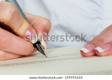 a woman signs a contract or a will with a fountain pen. - stock photo