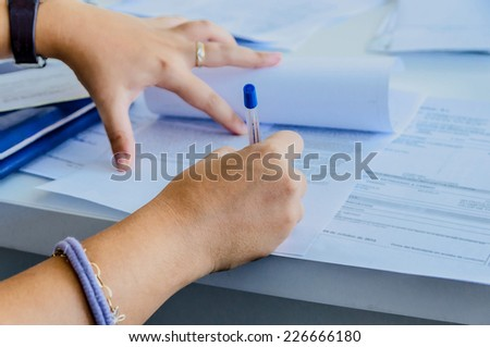 a woman signs a purchase document with a blue ballpen - stock photo