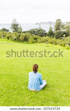 A woman sits alone and feels depressed in a public park overlooking the sea. - stock photo