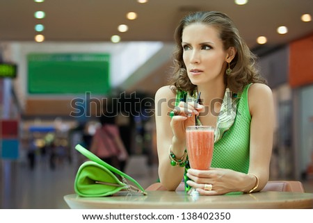 A woman sits at a table in a cafe with a cocktail in hand