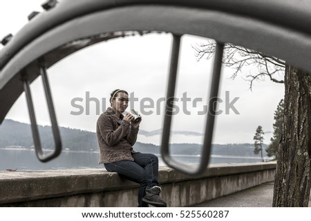 A woman sits on a concrete ledge by a lake enjoying her coffee.