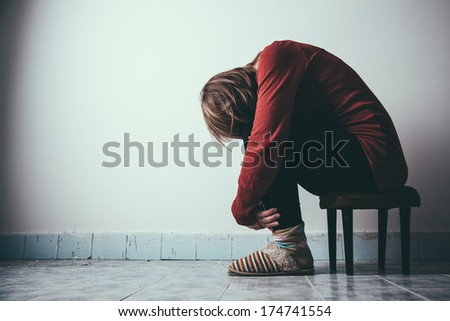 A woman sitting alone and depressed - stock photo