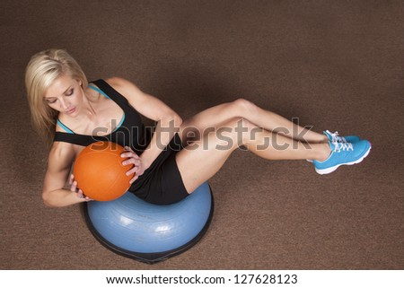 a woman sitting and doing a twist with a weighted ball