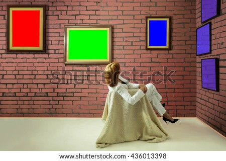 A woman sitting and looking at blank of one color frames in art gallery. Wall of bricks and frames are painted in RGB colors