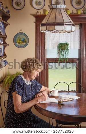 A woman sitting by window light writing a letter in a setting from 1940 - stock photo