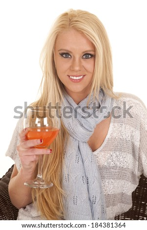 a woman sitting in a chair holding a refreshing drink in a glass.