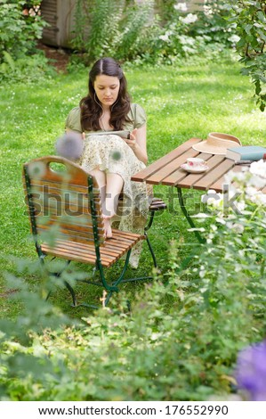 A woman sitting in a chair wearing earphones. - stock photo