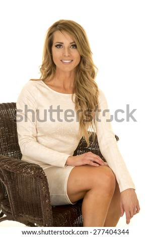a woman sitting in her brown wicker chair with a smile.