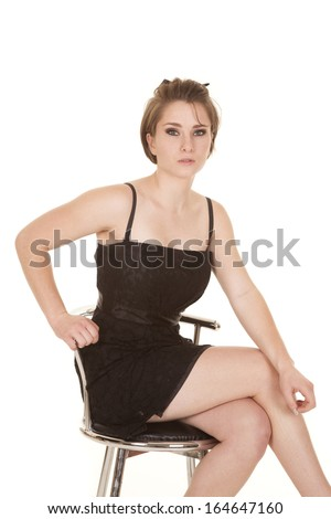 a woman sitting in her chair in her black dress with a serious expression on her face.