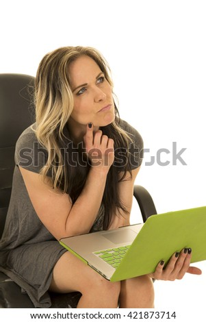 A woman sitting in her office chair, deep in thought about something on her laptop.