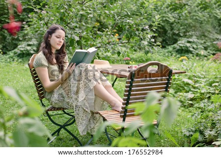 A woman sitting in the garden reading a book. - stock photo