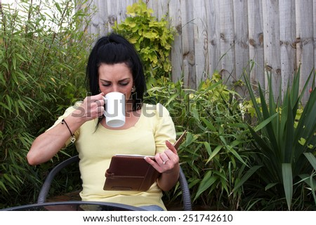 A woman sitting in the garden reading a book and having a hot drink - stock photo