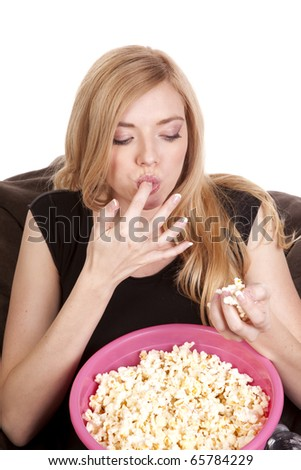 a woman sitting on a bean bag while she is enjoying her popcorn. - stock photo