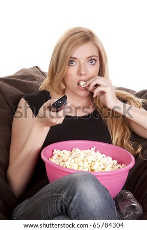 a woman sitting on a bean bag while she is enjoying her popcorn while she is watching tv with intense eyes. - stock photo