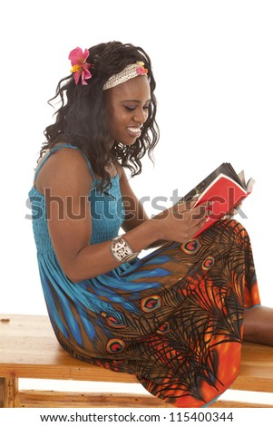 a woman sitting on a bench holding on to her book reading. - stock photo