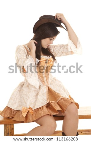 A woman sitting on a bench placing her cowgirl hat on top of her head. - stock photo