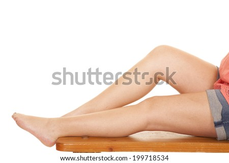 A woman sitting on a bench showing her legs. - stock photo