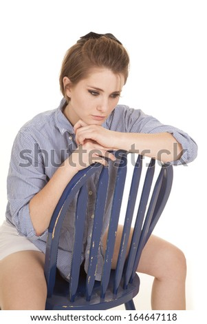 a woman sitting on a blue chair deep in thought.