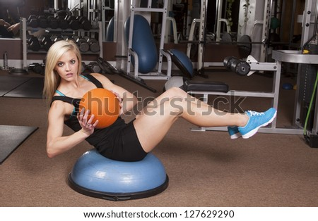 a woman sitting on a half ball balancing with a weight ball. - stock photo