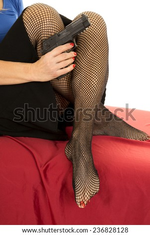 A woman sitting on a red sheet holding on to a pistol. - stock photo
