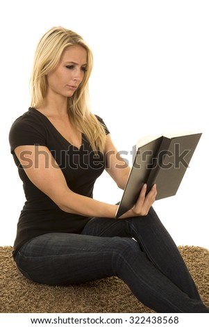 a woman sitting on her carpet reading her book. - stock photo
